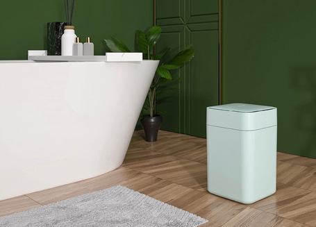 Bathroom with large white tub and teal Townew trash can