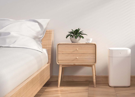 Bedroom with a bed, sidetable and white Townew trash can